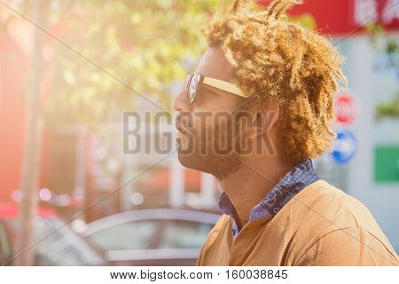 Portrait of young black man with dread locks wearing sunglasses. Sun effect applied.