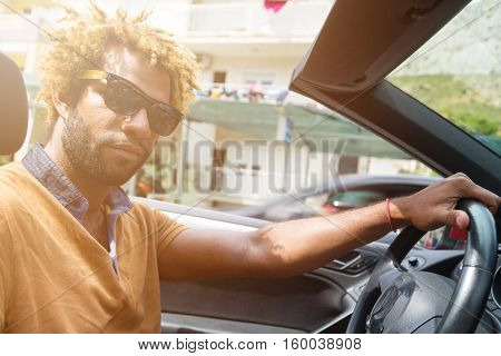 Young happy black man with dread locks wearing sunglasses sitting in the convertible car. Sun effect applied.