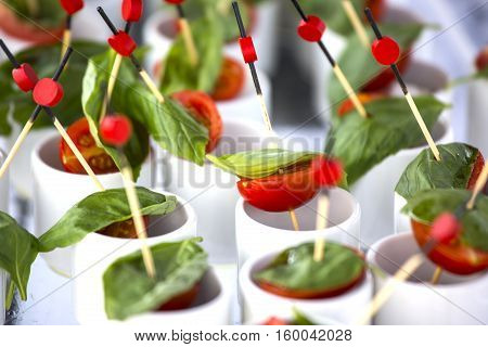 Finger food: cherry tomatoes mozzarella and basil. Wedding starter.