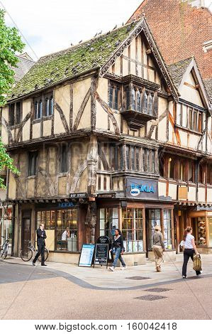 Oxford United Kingdom - June 20 2006: People going about their business on a pedestrian zone in shopping center of Oxford. Crowd of Pedestrians walking with old fachwerk houses with shops and restaurants.