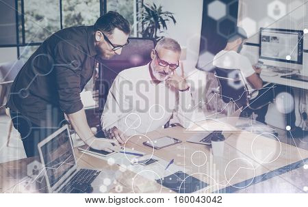 Concept of digital screen, virtual connection icon, diagram, graph interfaces.Young bearded man discussing ideas with account manager in modern office.Business people discussion.Film effect, blurred