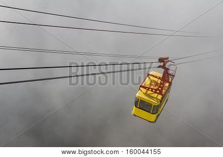 yellow cable car rides through the fog
