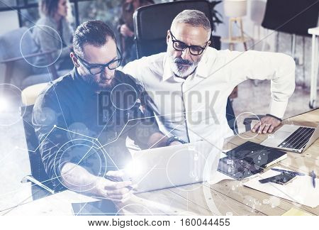 Concept of digital screen, virtual connection icon, diagram, graph interfaces.Young bearded man working together with colleague in new startup project.Business people teamwork concept.Flare, blurred