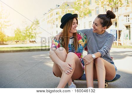 Two Trendy Young Women Sitting Socialising