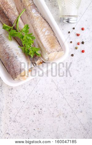raw fish hake in white packaging decorated with parsley