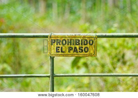 No trespassing sign on a metal door written in spanish