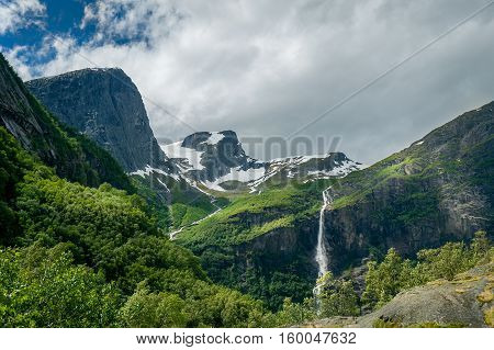 Beautiful green mountain slopes and waterfalls on the hiking path to Briksdalsbreen glacier viewpoint. Briksdal, Norway.