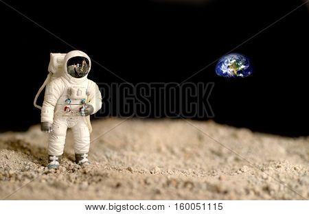 Astronaut on the moon with the earth on the background elements of this image furnished by NASA.