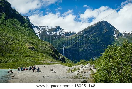 Group of tourists at the lake shore, popular hiking path finish and Briksdalsbreen glacier viewing point. Briksdal, Norway.
