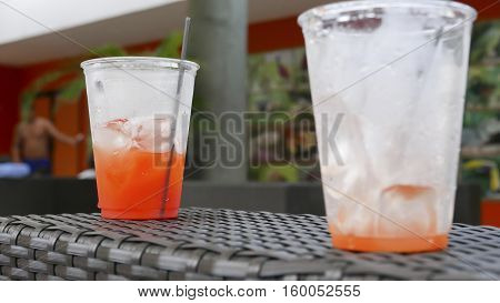 Two plastic cups with drinks on a chair arm by a swimming pool area