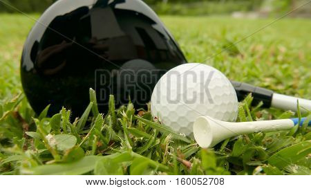 Macro shot of a golf club with ball and tee on the fairway grass