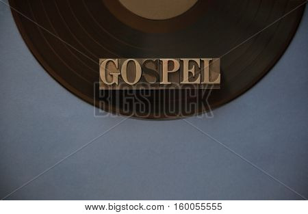 The word gospel in old metal type on a black vinyl record with a blue-gray background for text