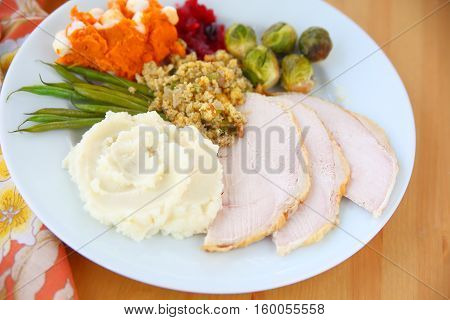 Plate of roast turkey slices mashed potatoes stuffing brussels sprouts mashed sweet potatoes and green beans with cranberry sauce