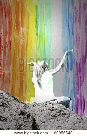 Girl with arms raised above the head double exposure with rainbow watercolor background in celebration of reaching the top of the mountain during the campaign freedom concept