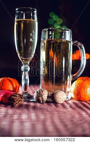 New Year's eve. Funny image of a wineglass and a beer glass of champagne mandarins cinnamon and walnuts on the background of lights bokeh. Low key. Selective focus.