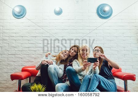 Beautiful girls sitting on the couch, have fun and make selfie Hostel
