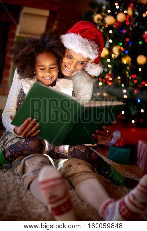 Mother is reading a book to her little girl on Christmas eve- family time