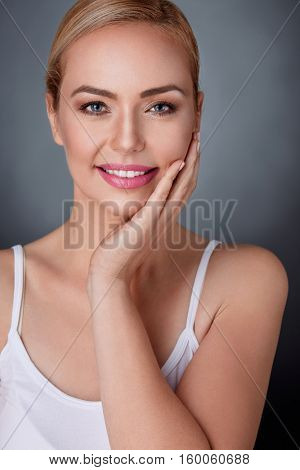 satisfied woman touching her nourished perfect skin