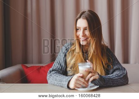 Gorgeous winter girl in knitted sweater dreams with a cup of hot coffee