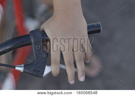 Close up bicycle rider's hands on a bicycle handlebar.
