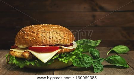 Home made hamburger with cheese, tomatoes and basil  on wooden background. Fastfood meal. Vintage toned