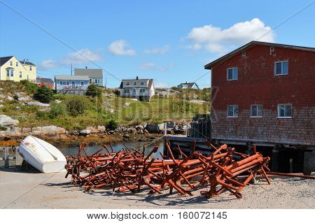 Rusty anchors in a pile on shore in the village of Peggy's Cove.
