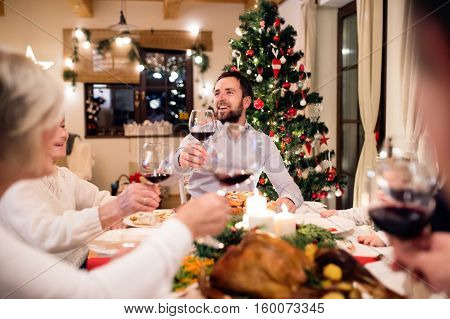 Beautiful big family sitting at the table, celebrating Christmat together at home. Illuminated Christmas tree behind them.
