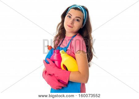 portrait of cheerful young maid girl in an apron with cleansers isolated on white background