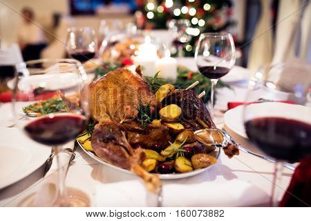 Christmas meal laid on table in decorated dining room. Roasted turkey or chicken, vegetables, Christmas wreath, glass of red wine.