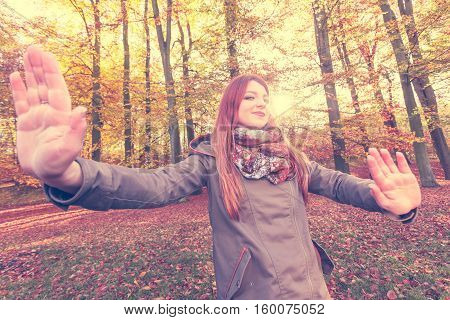 Nature outdoors concept. Young lady is enjoying the day outside. Ginger hair girl is cheerful wearing jacket and colourful scarf.
