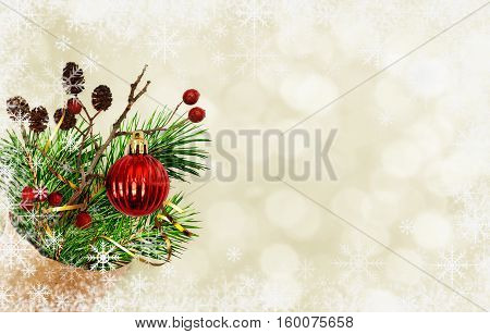 Christmas bouquet with pine twigs cones berries and red ball in a craft paper cornet on holiday background with snowflakes frame