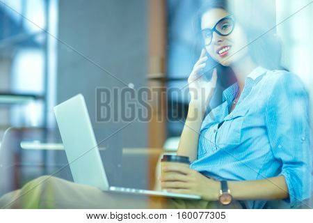 Beautiful young business woman sitting at office desk and talking on cell phone,