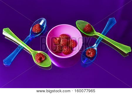 multicolored background whit red raspberries and spoons