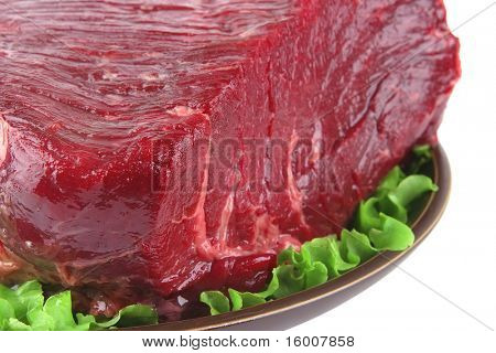 huge uncooked meat on plate over white