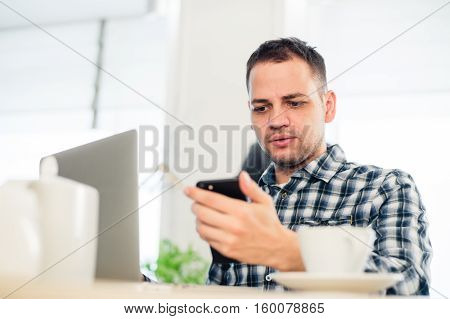 Closeup portrait, stressed young man in purple sweater, shocked surprised, horrified and disturbed, by what he sees on his cell phone, isolated indoors background