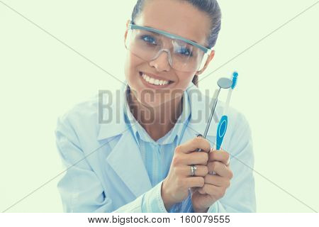 Beautiful female dentist doctor holding and showing toothbrush isolated on a white background