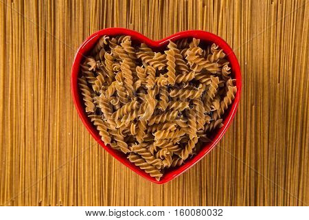 Wholemeal Pasta. Integral Fusilli Into A Heart Bowl Over A Wooden Table Top View