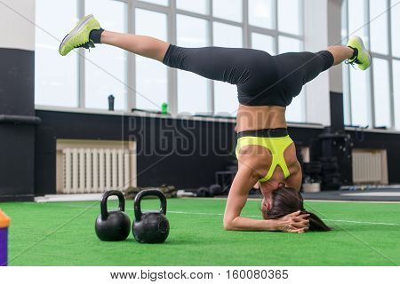fit woman doing yoga exercise, headstand asana in gym