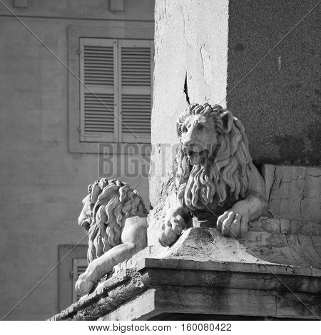 Statues of Lions adorning the Arles Obelisk at Place de la Republique in Arles, France. Black and white.