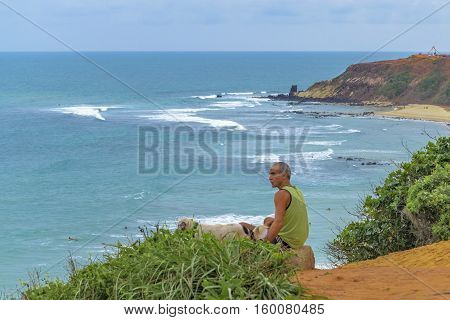 TIBAU DO SUL, BRAZIL, JANAURY - 2016 - Old man with hi dog at landscape scene of coast at Tibau do Sul a watering place located in Brazil
