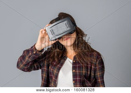 portrait of cutie woman in virtual reality helmet in studio on grey background