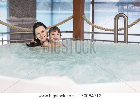 Mom and son relax in the tub with hydro massage in Spa salon