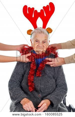Portrait of an elderly woman wearing Christmas decoration on an isolated background