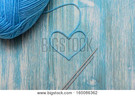 Heart from blue yarn of knitting and knitting spokes