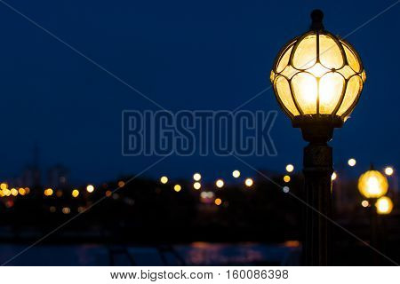 Night streetlight near city river with urban lights