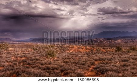Light pours from rain clouds over a desert mesa.