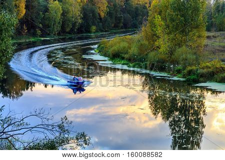 Motor boat floats on the river, the banks of the forest undergrowth