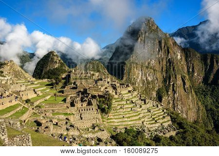 View of the Lost Incan City of Machu Picchu with clouds near Cusco, Peru. Machu Picchu is a Peruvian Historical Sanctuary.