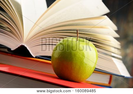 Composition with hardcover books and green apple.