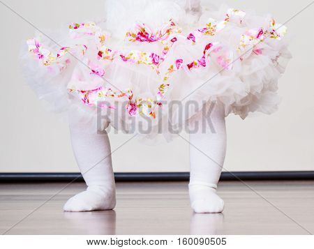 Lovely little child girl in princess fairy dress and white tights. Part body of baby ballerina.